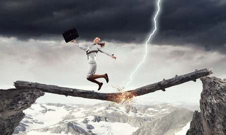 Young successful businesswoman jumping over gap. Risk and challenge concept