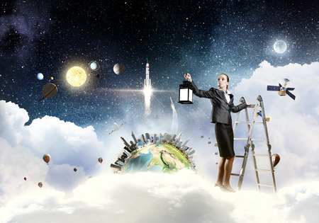 Young businesswoman in darkness with lantern in hand standing on ladder. Elements of this image are furnished by NASA