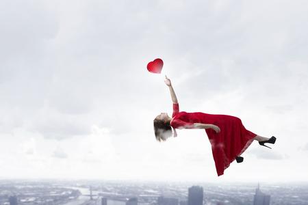 dreamy: Dreamy beautiful woman in red dress flying in sky