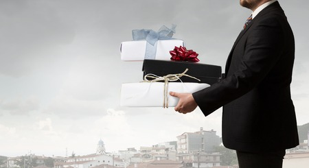 layoff: Young businessman with big gift boxes in hands Stock Photo