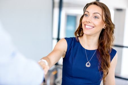 Young business lady giving handshake after agreement Stock Photo