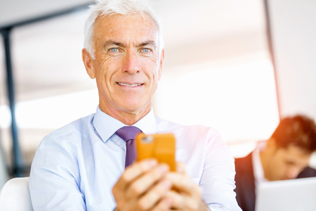Handsome businessman at the office with mobile phone
