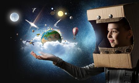 헬멧 및 우주 비행사 의상을 입고 귀여운 학교 소녀. 이 이미지의 요소는 NASA에 의해 제공됩니다.