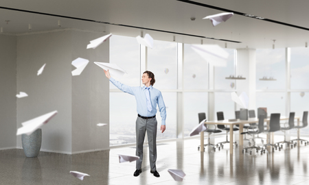 careless: Careless businessman in office playing with paper plane. Mixed media