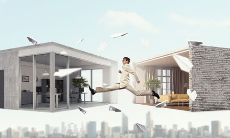 modern interiors: Young businessman jumping between two modern interiors. Mixed media Stock Photo