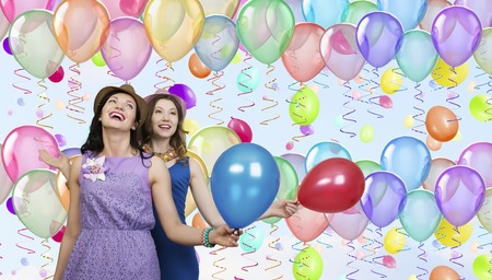 Two young friends or colleagues holding party balloons