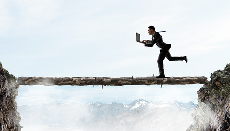 business obstacle: Young successful businessman running over gap. Risk and challenge concept