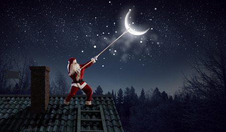 Santa on house roof catching moon on rope