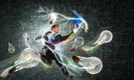 formalwear: Happy young man in formalwear jumping and catching light bulb Stock Photo