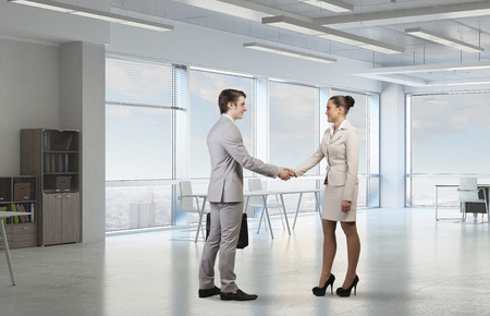 Businessman and woman shaking hands in office interior. Mixed media
