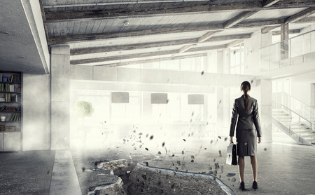 impediment: Businesswoman in office interior standing at edge of crack in floor. Mixed media