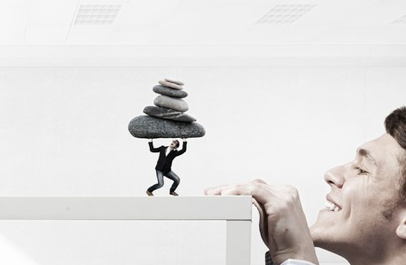 peep: Businessman peep from under table at guy lifting stone above head. Mixed media