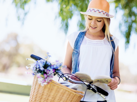 novel: Happy young woman with bicycle in the park reading book