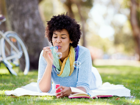 woman blowing: Young woman blowing bubbles in summer park
