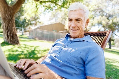 Handsome senior man with notebook sitting in the park