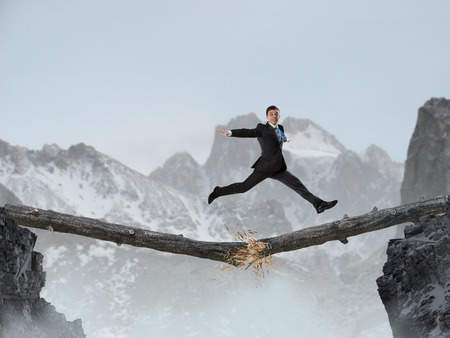 Young successful businessman jumping over gap. Risk and challenge concept