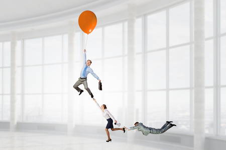 Business people escaping from office on balloon. Mixed media