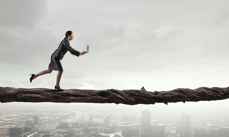 impediment: Young successful businesswoman running over gap. Risk and challenge concept Stock Photo