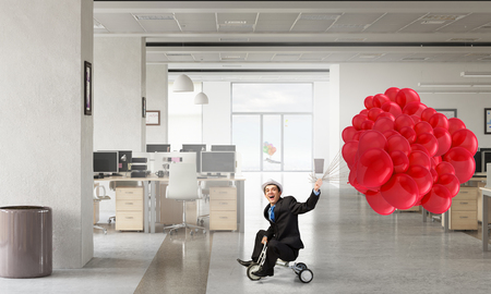 careless: Young careless businessman riding three wheeled bike in office. Mixed media