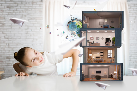 cute house: Cute girl looking at model of house on table. Elements of this image are furnished by NASA . Mixed media Stock Photo
