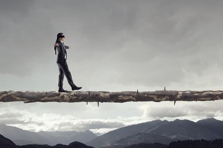 Blind businessman walking on log over gap. Risk and challenge concept