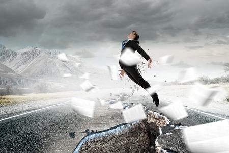 Determined businessman jumping over crack in asphalt road