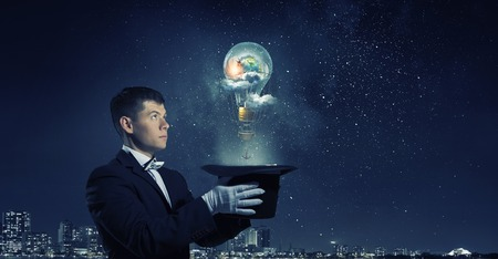 Man magician with cylinder hat doing tricks. Elements of this image are furnished by NASA