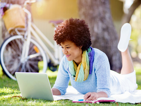 Woman working outdoors in park with laptop Stock Photo