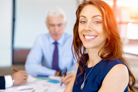 attractive  female: Young businesswoman sitting at desk in office and working