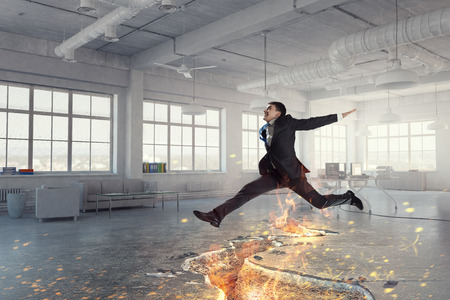 Determined businessman jumping over crack in floor. Mixed media