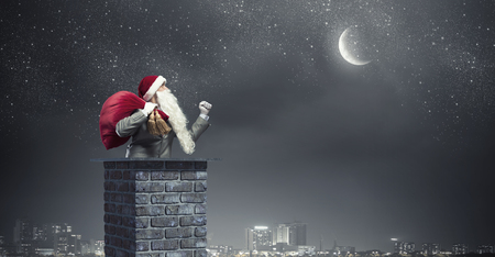 Santa Claus inside brick chimney with his bag of toys Stock Photo