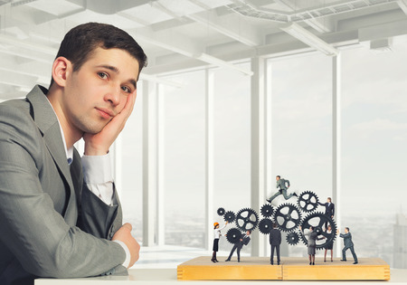 Young businessman sitting at table and playing chess. Mixed media photo