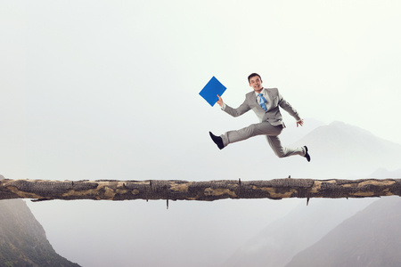 risky job: Young successful businessman running on log above gap. Risk and challenge concept