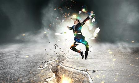 impediment: Determined businessman jumping over crack in asphalt road