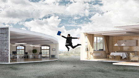 between: Young businessman jumping between two modern interiors. Mixed media Stock Photo