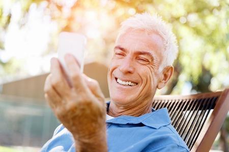 Handsome senior man outdoors using mobile phone