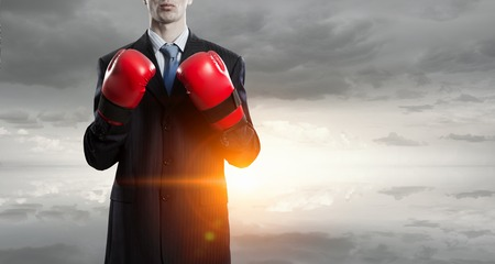 Determined businessman in suit and boxing gloves Stock Photo