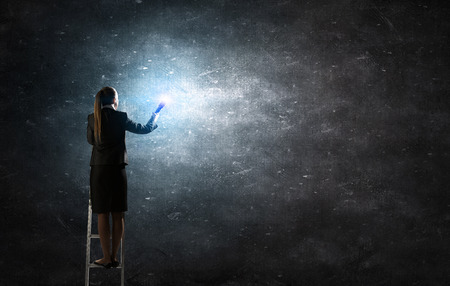 cement solution: Young businesswoman in darkness with lantern in hand standing on ladder