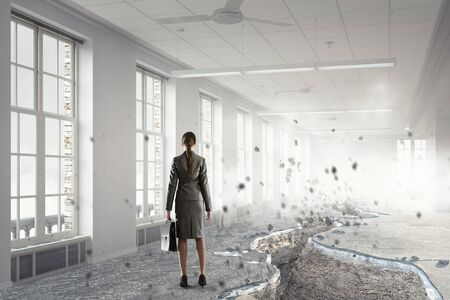 investment concept: Businesswoman in office interior standing at edge of crack in floor. Mixed media