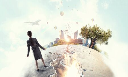 Businesswoman standing on cracked globe as symbol of catastrophe