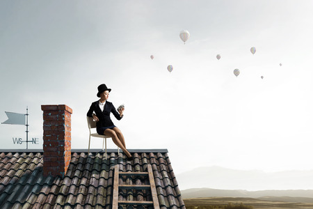 timepiece: Young businesswoman wearing cylinder sitting in chair on house roof Stock Photo