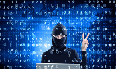 Woman hacker in mask using laptop against dark background Stock Photo