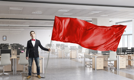 Jonge man in kantoor interieur met rode vlag. Gemengde media
