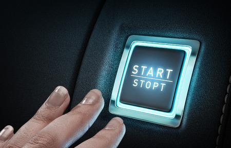 Close of hand pushing glowing blue button Stock Photo