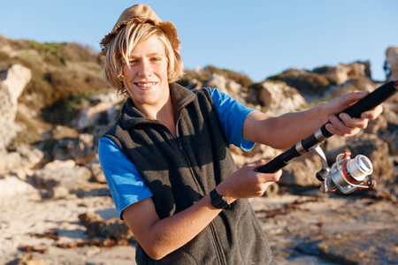 grandkids: Teenage boy fishing with rod at sea