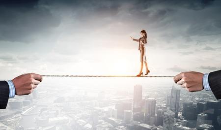 Zakenvrouw met blindfolder op de ogen balanceren op het touw