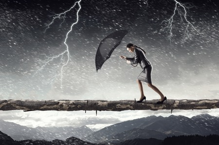 forceful: Young determined businesswoman with umbrella walking against strong wind