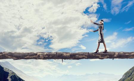 Blind businesswoman walking on wooden log above gap. Risk and challenge concept