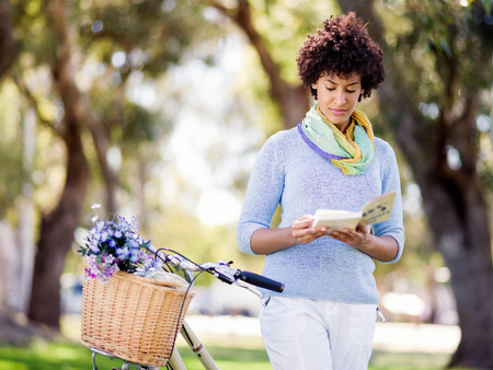 Happy young woman with bicycle in the park reading book