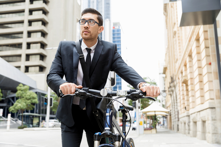 commuting: Young businessman wearing suit with bike outdoors Stock Photo